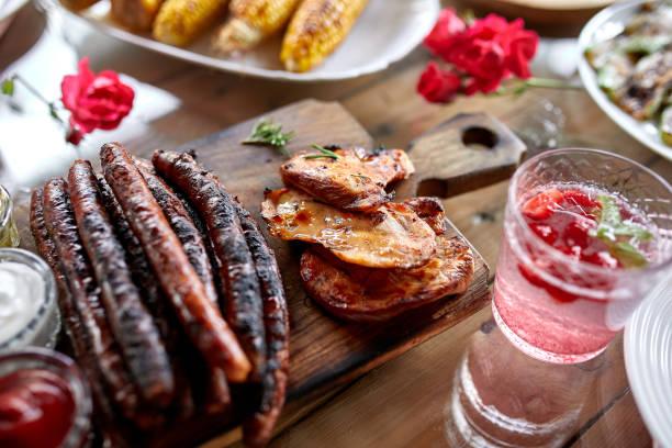 Esstisch mit Fleischgrill und Wurst, Gemüse, Limonade – Foto