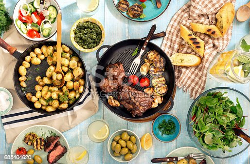 istock Dinner table with meat grill, roast new potatoes, salads, vegetables, sauces, snacks and lemonade 685404620