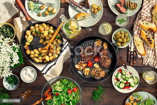 685404620istockphoto Dinner table with meat grill, roast new potatoes, vegetables, salads, sauces, snacks and lemonade 685404598