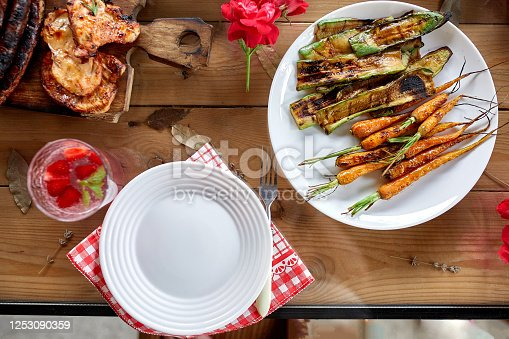 657146780 istock photo Dinner table with meat grill, roast vegetables, sauces and lemonade, variety serving 1253090359