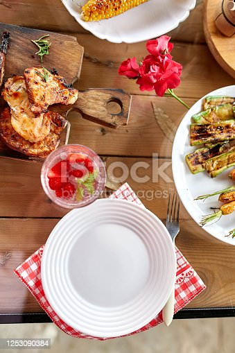 657146780 istock photo Dinner table with meat grill, roast vegetables, sauces and lemonade, variety serving 1253090384