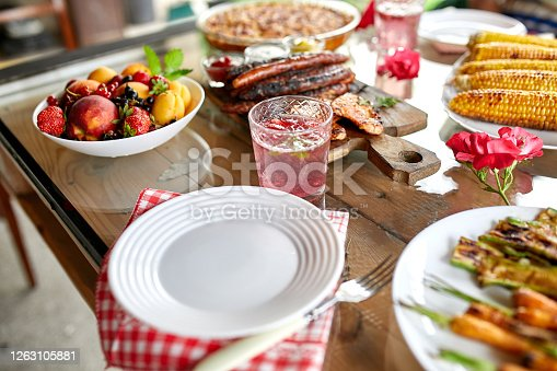 657146780 istock photo Dinner table with meat grill, roast vegetables, sauces and lemonade, variety serving 1263105881