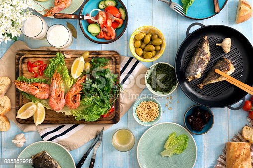 657146780 istock photo Dinner table with shrimp, fish grilled, salad, different snacks and lager beer 685852928
