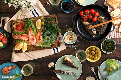 690274036 istock photo dinner table with shrimp, fish grilled, salad, different snacks and white wine 690273934