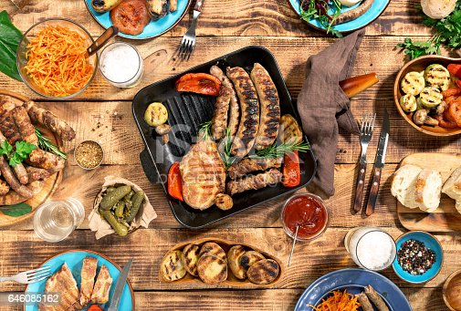 685404620istockphoto Dinner table with variety food grilled, top view 646085162