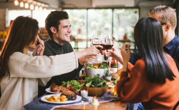 cena con amigos. grupo de jóvenes disfrutando de la cena juntos. dining wine cheers party concepto de acción de gracias - restaurante fotografías e imágenes de stock