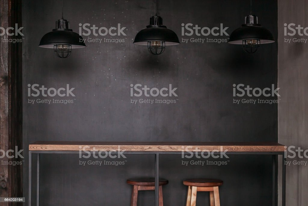 Dinning table set in loft style dining room with black lamps stock photo