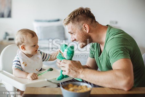 Father feeding young son, they are at kitchen table father animate kid with dinosaur toy