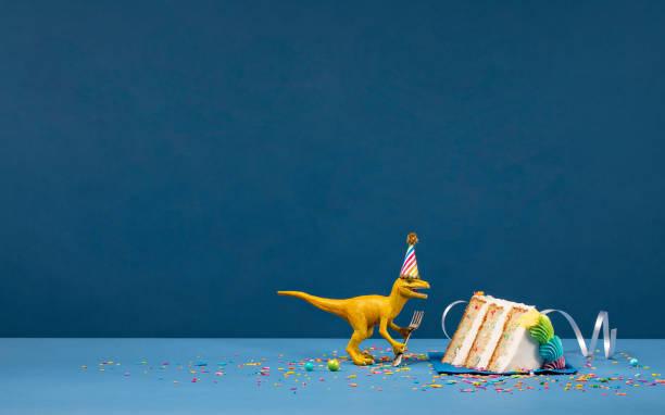 Dinosaur and slice of Birthday Cake stock photo