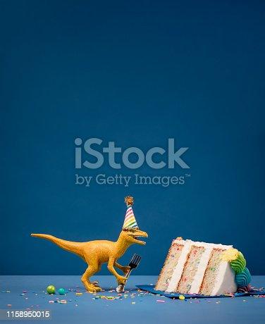 istock Dinosaur and slice of Birthday Cake 1158950015