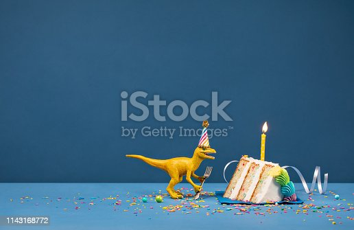 Toy Dinosaur holding a fork and blowing out a Birthday candle on a blue background