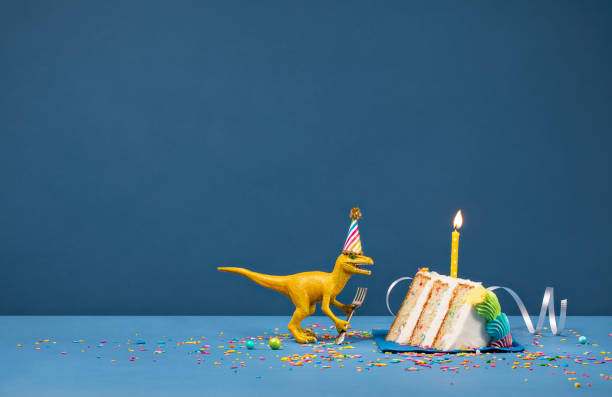 Dinosaur Birthday Party Toy Dinosaur holding a fork and blowing out a Birthday candle on a blue background birthday background stock pictures, royalty-free photos & images
