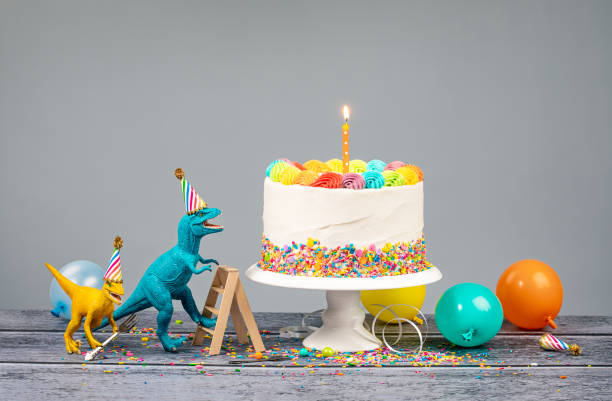 Dinosaur Birthday Party Hungry toy dinosaurs wearing hats and holding forks next to a birthday Cake on a gray background first birthday stock pictures, royalty-free photos & images