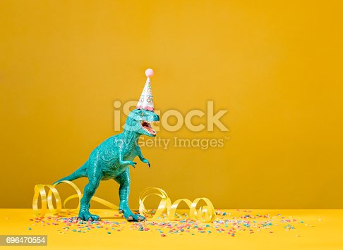 Toy dinosaur with birthday party hat on a yellow background.