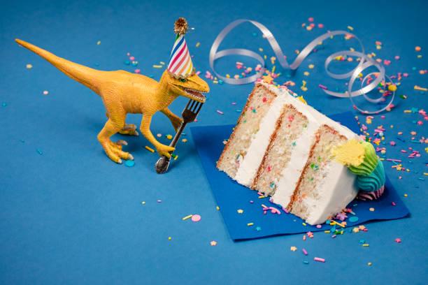 Dinosaur Birthday Party with slice of Cake stock photo