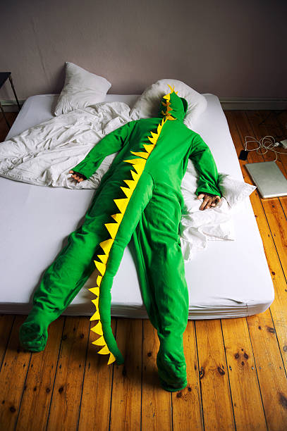 Dinosaur Costume Man Lies Face Down in Bed Dinosaur man lies face down in a simple bed on the floor, gadgets charging beside him face down stock pictures, royalty-free photos & images