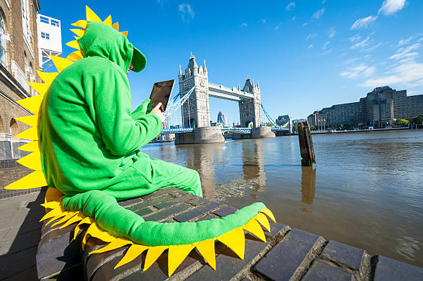 dinosaur man sitting with tablet in london - mascotte photos et images de collection