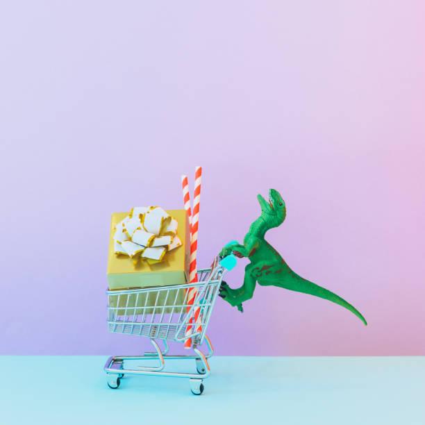 Dinosaurier schiebt einen Wagen mit Einkaufsmöglichkeiten, Geschenken und Weihnachtsdekorationen. Neujahrsferienkonzept – Foto