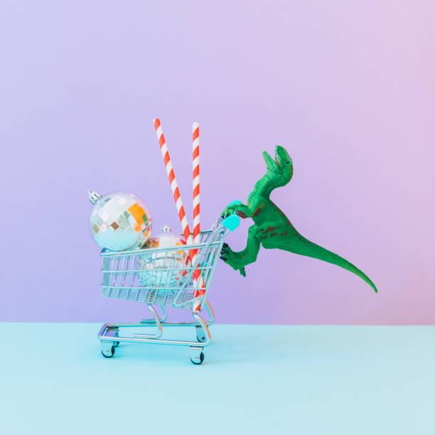 Dinosaurier schiebt einen Einkaufswagen mit Einkaufsmöglichkeiten, Geschenken und Weihnachtsdekorationen. Neujahrsferienkonzept. Minimal und surreal – Foto