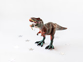 Dinosaur with engagement ring. Plastic toy with wedding jewelry. White background with star confetti.