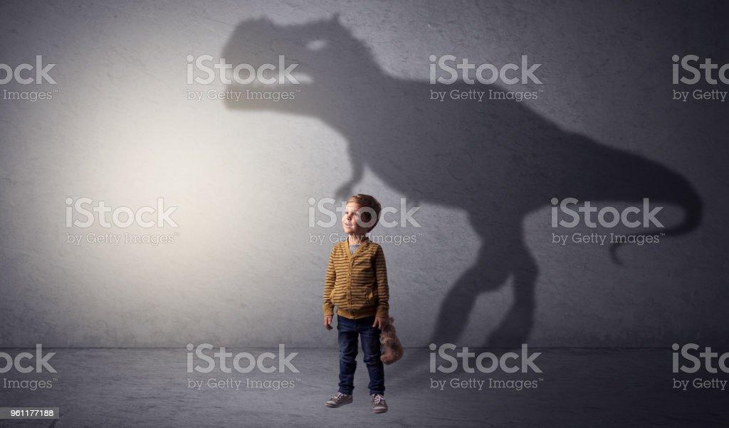 Dinosaurus shadow behind cute boy stock photo