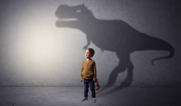 Dinosaurus shadow behind cute boy stock photo