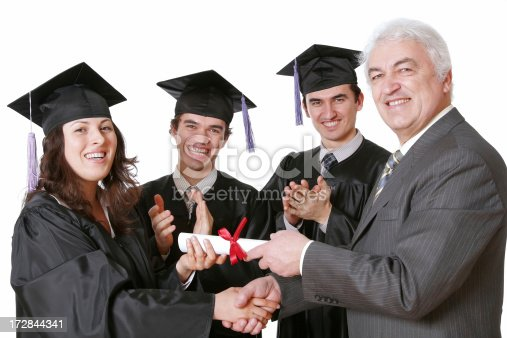 Four persons (an elderly man handing a certificate to a young lady dressed in a cap and gown; and two students in caps and gowns clapping in the background) isolated on white