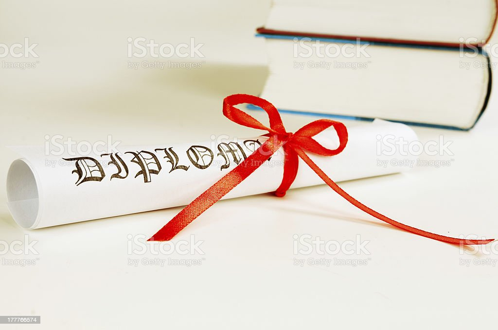 Diploma with red ribbon and books royalty-free stock photo