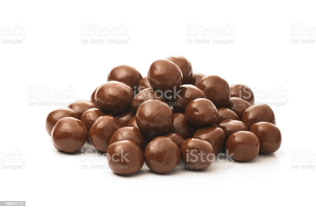 Dipped chocolate peanuts in a pile on a white background stock photo