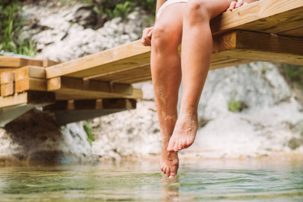 Dipping feet in fresh water Dipping feet in fresh water on a warm summer day scar stock pictures, royalty-free photos & images