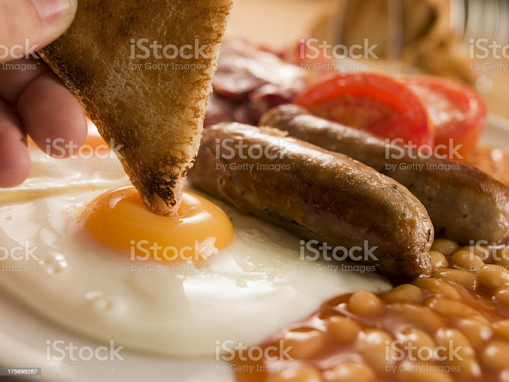 Dipping Toast into Fried Egg on a Full English Breakfast stock photo