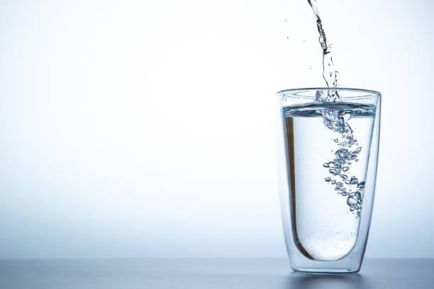 dipping water into a double glass close up. - água imagens e fotografias de stock
