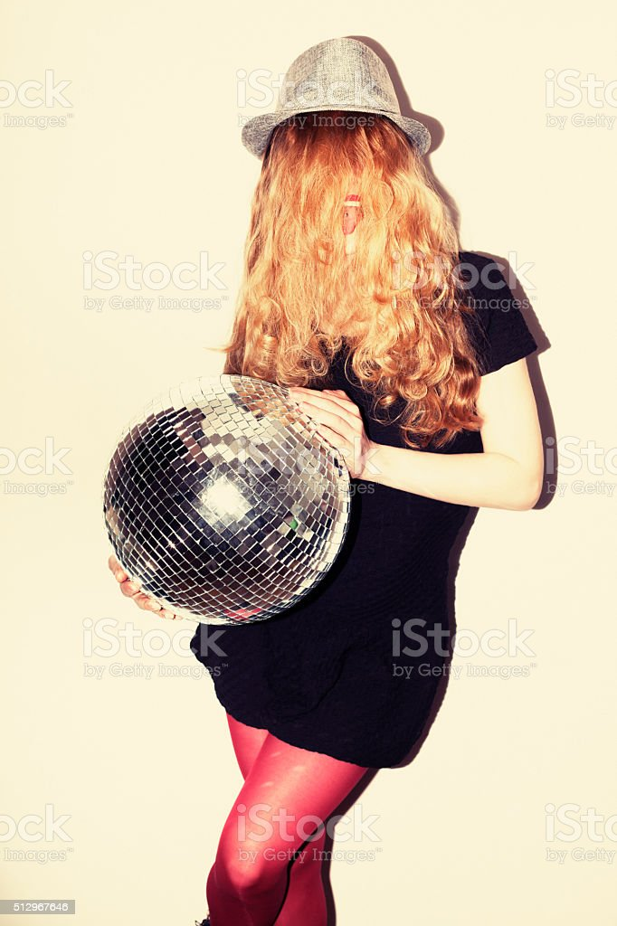 Direct flash portrait of beautiful young woman with disco ball stock photo