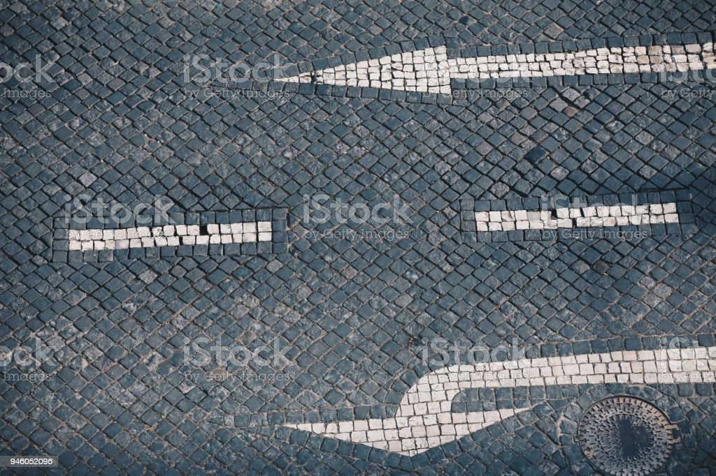 Direction arrow and street sign on handmade stone pavement stock photo