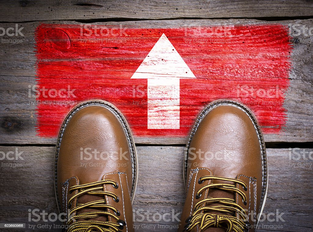 Direction Arrow. Top View of Boot on wooden background stock photo