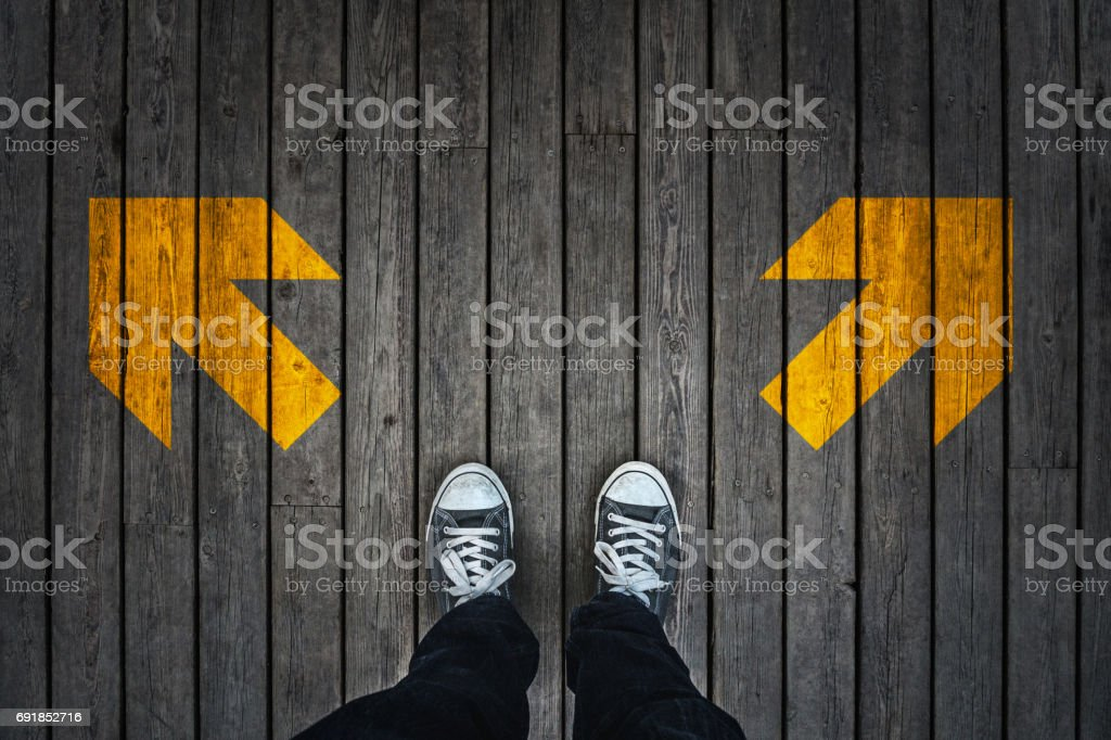 Young man standing on wooden floor with yellow arrow sign.