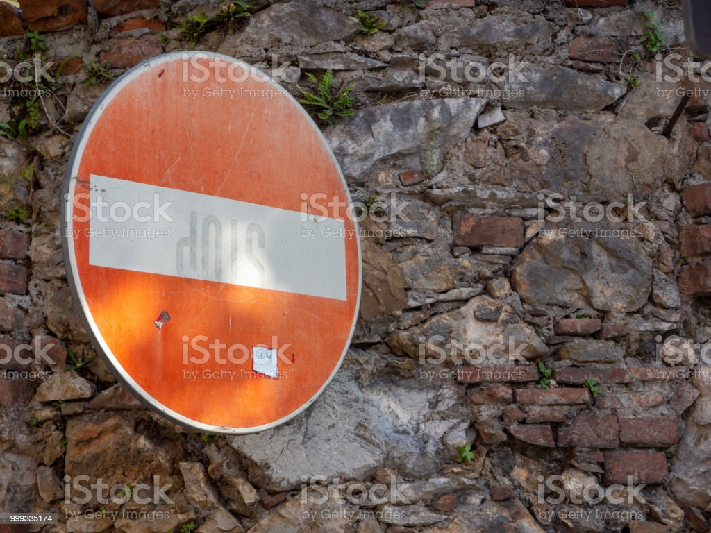 Direction sign forbidden on old wall to face - foto stock