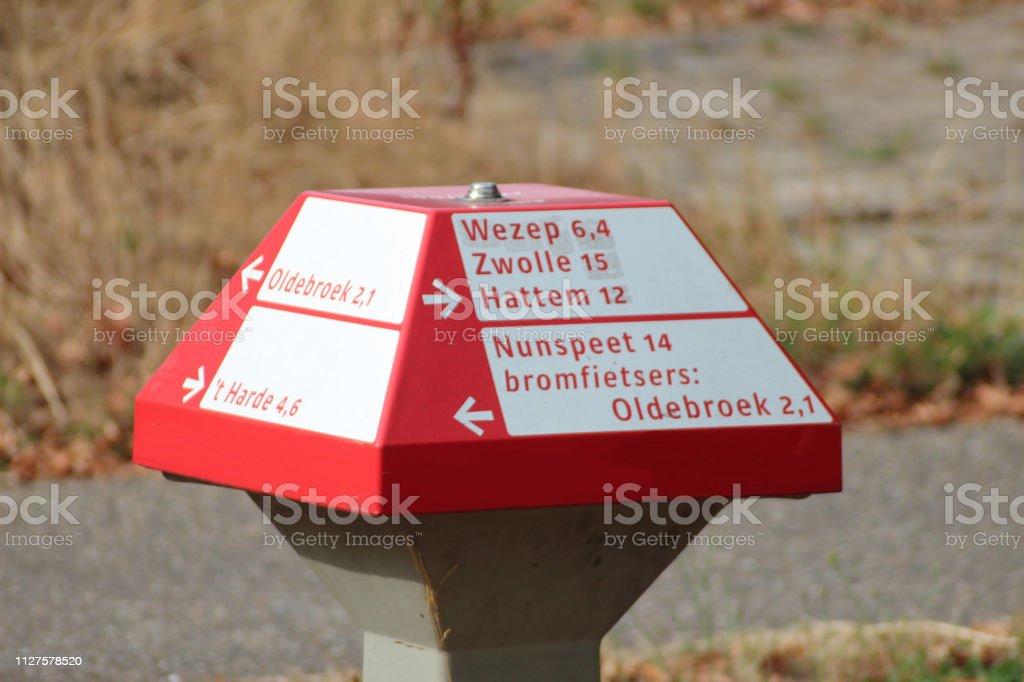 Richting bord met Nederlandse plaatsnamen in de vorm van een paddenstoel uit rode en witte kleuren voor de fietser op de Veluwe in Nederland foto
