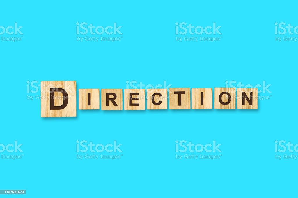 Direction. Words written on a wooden block. Blue Background Isolated. Business concept. stock photo