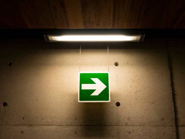 Directional arrow sign illuminated by a neon light from above, right arrow symbol direction stock photo