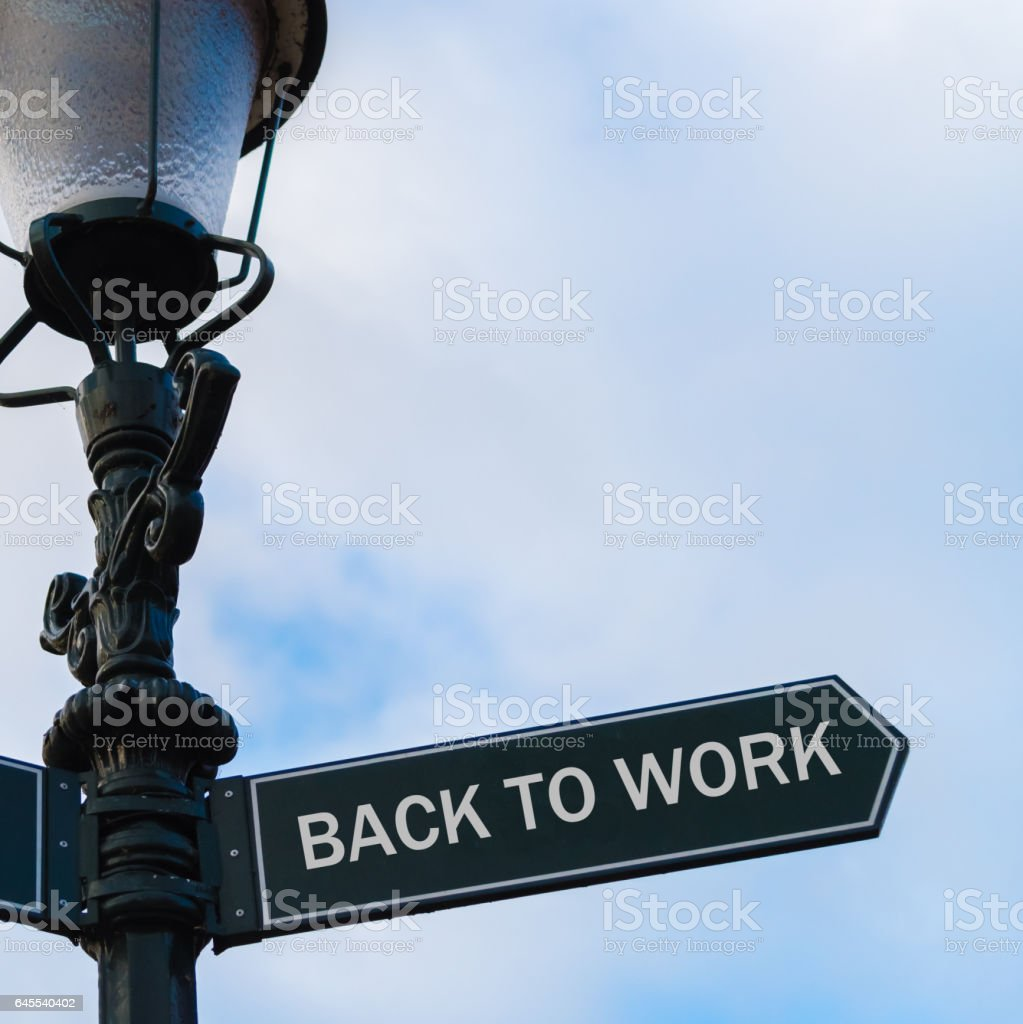 BACK TO WORK directional sign on guidepost stock photo