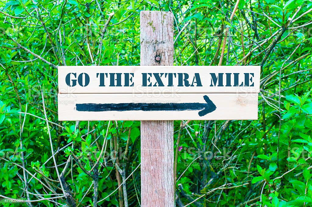 GO THE EXTRA MILE Directional sign stock photo