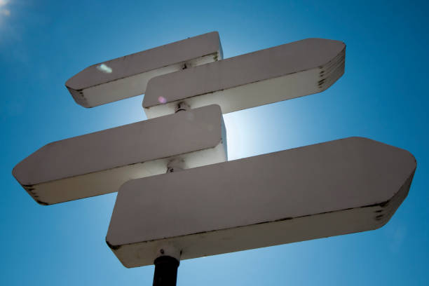 Directional sign post, backlit, sunbeam, clear blue sky background. stock photo