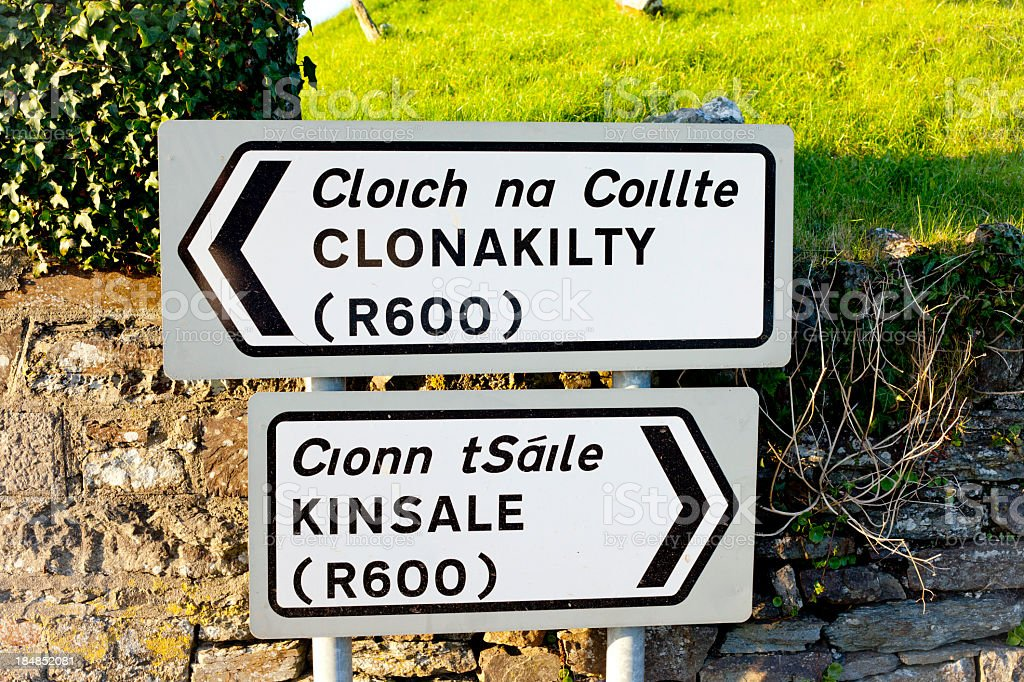 Directional signs in Ireland near a brick wall stock photo