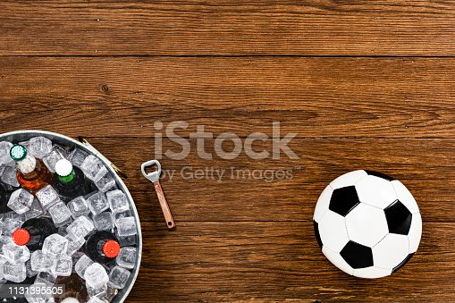 Looking down from directly above on a black and white soccer ball along with a wooden handle bottle opener and assorted beer bottles, both clear and amber, on ice in an elongated galvanized tub sitting on a worn wood table.