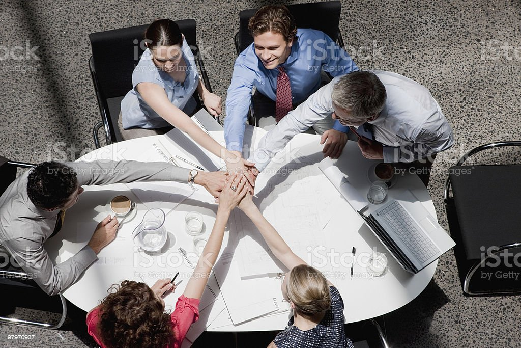 Directly above business people stacking hands in meeting at conference table royalty-free stock photo