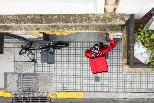 istock Directly above delivery man ringing the door bell with order 1193301918