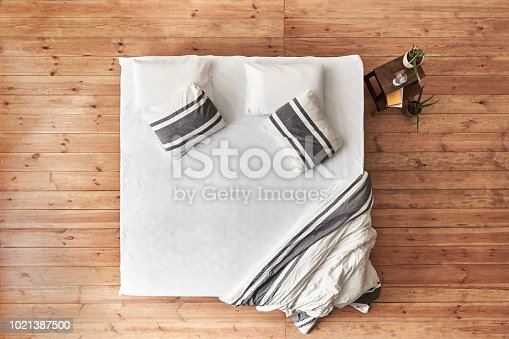 Top View, Empty bed, wooden floor, white sheet
