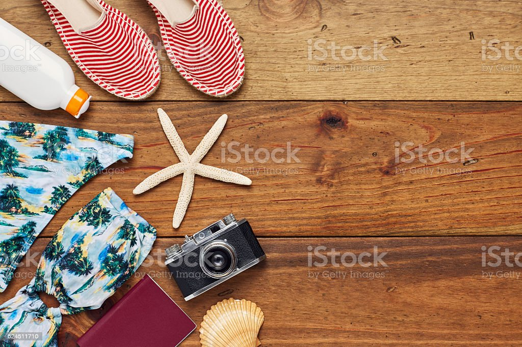 Directly above flat lay of beach accessories on wooden floor stock photo