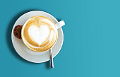 directly above shot of cup of cappuccino on blue background